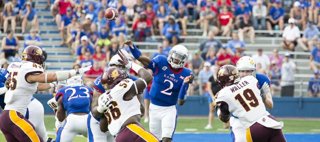 Kansas quarterback Montell Cozart (2) passes over the top of the Central Michigan defense during their game on Saturday afternoon at Memorial Stadium.