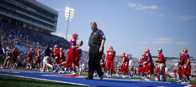 Kansas head coach Charlie Weis walks off the field as the Jayhawks warm up prior to kickoff against Texas on Saturday, Sept. 27, 2014 at Memorial Stadium.