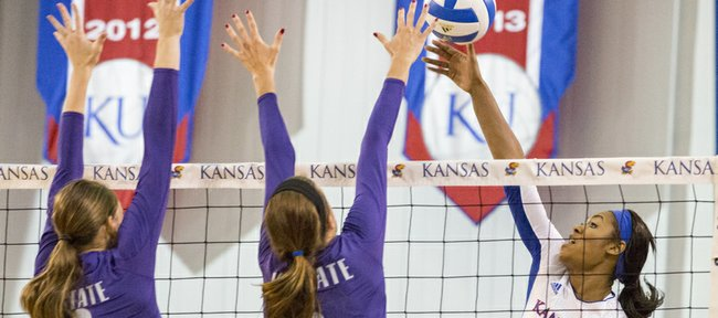 Kansas junior outside hitter Tiana Dockery (7) looks to hit past Kansas State's Natali Jones (12) and Katie Brand (6) during their volleyball match Wednesday evening at the Horejsi Center.