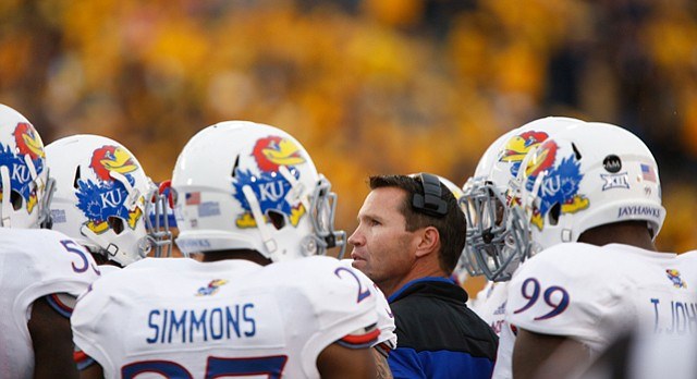 Kansas head coach Clint Bowen looks up at the scoreboard as he is surrounded by his defenders during the second quarter on Saturday, Oct. 4, 2014 at Milan Puskar Stadium in Morgantown, West Virginia.