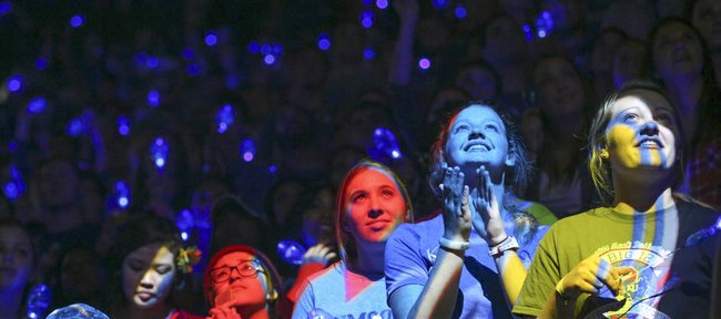 Spotlights shine on Jayhawk fans as they wait with anticipation while the team is introduced during Late Night in the Phog on Friday, Oct. 10, 2014 at Allen Fieldhouse.