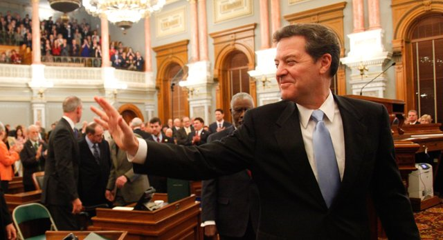 Governor Sam Brownback waves to lawmakers as he is escorted to the speaker's podium of the House chamber before delivering the State of the State address on Tuesday at the Kansas Statehouse. In his speech, Brownback called for a cut in taxes and changes in the way judges are selected.