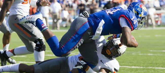 Kansas junior quarterback Michael Cummings is not afraid of contact has he plows through Oklahoma State safety Jordan Sterns during their game Saturday afternoon at Memorial Stadium.
