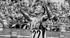 Billy Mills throws his arms into the air as he hits the finish line to win a gold medal for the U.S. in the Olympic 10,000 meter run, in this Oct. 14, 1964 file photo in Tokyo.