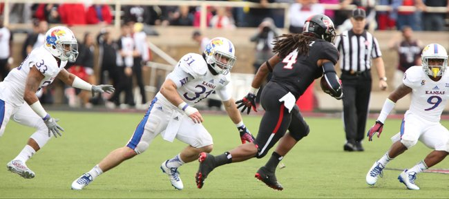 Texas Tech receiver Bradley Marquez makes a move against Kansas defenders Cassius Sendish (33), Ben Heeney (31), and Fish Smithson (9) during the second quarter on Saturday, Oct. 18, 2014 at Jones AT&T Stadium in Lubbock, Texas.
