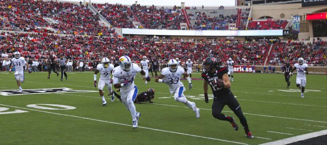 Texas Tech receiver Ian Sadler tears up the sideline past Kansas defenders JaCorey Shepherd (24) and Cassius Sendish (33) on a big gain during the third quarter on Saturday, Oct. 18, 2014 at Jones AT&T Stadium in Lubbock, Texas.