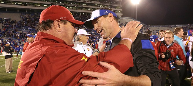 Kansas interim head football coach Clint Bowen is congratulated by former KU head coach Mark Mangino, the offensive coordinator for Iowa State following the Jayhawks' 34-14 win over the Cyclones on Saturday, Nov. 8, 2014.