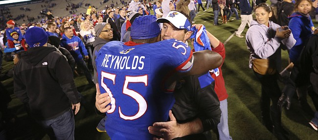 Kansas interim head football coach Clint Bowen gets a bear hug from his player Michael Reynolds following the Jayhawks' 34-14 win over the Cyclones on Saturday, Nov. 8, 2014.
