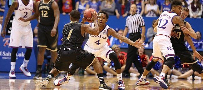 Kansas guard Devonte Graham reaches to defend against a pass from Emporia State guard Perryonte Smith during the first half on Tuesday, Nov. 11, 2014.