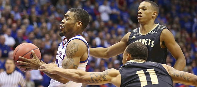 Kansas guard Frank Mason gets to the bucket past Emporia State guards Terrence Moore (11) and Tyler Jordan during the first half on Tuesday, Nov. 11, 2014.