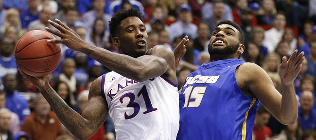 Kansas forward Jamari Traylor looks to sling a pass across the court as he is defended by UC Santa Barbara forward Alan Williams during the first half on Friday, Nov. 14, 2014 at Allen Fieldhouse.