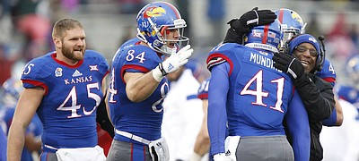 Kansas tight end Jimmay Mundine is congratulated by running backs coach Reggie Mitchell and teammates Ben Johnson (84) and Ed Fink (45) after his touchdown against TCU during the second quarter on Saturday, Nov. 15, 2014 at Memorial Stadium.