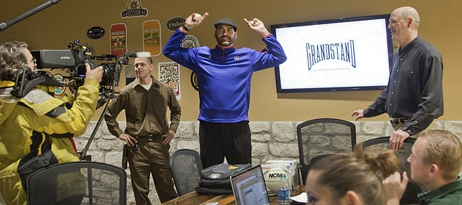 Former NBA and KU basketball star Scot Pollard, center, makes a UPS delivery to fellow KU basketball player Chris Piper's business Grandstand, during a ride-along with UPS driver Chris Taylor, left, Thursday, Nov. 20, 2014. UPS was making a promotional video of the special Jayhawk delivery.