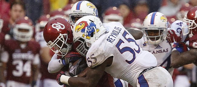 Kansas linebacker Michael Reynolds (55) tries to drag down Oklahoma running back Samaje Perine (32) during the third quarter on Saturday, Nov. 22, 2014 at Memorial Stadium in Norman, Oklahoma.
