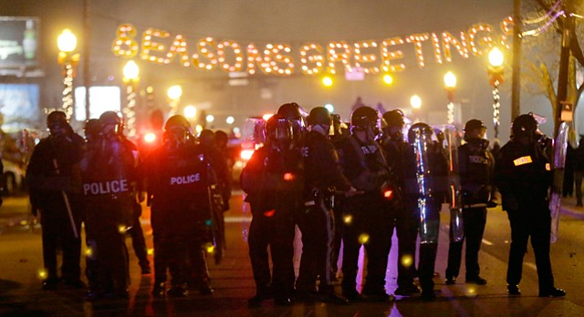 Police gather on the street as protesters react after the announcement of the grand jury decision Monday, Nov. 24, 2014, in Ferguson, Mo. A grand jury decided not to indict Ferguson police officer Darren Wilson in the death of Michael Brown, the unarmed, black 18-year-old whose fatal shooting sparked sometimes violent protests.