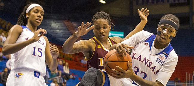 Kansas sophomore guard Keyla Morgan (32) rips a rebound away from Iona forward Joy Adams during first half action in their game Wednesday evening at Allen Fieldhouse.