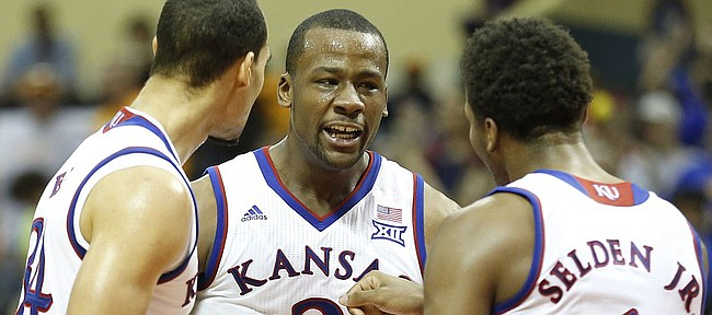 Kansas players Perry Ellis, left, Cliff Alexander and Wayne Selden celebrate a bucket by Alexander late during the second half on Friday, Nov. 28, 2014 at the HP Field House in Kissimmee, Florida.