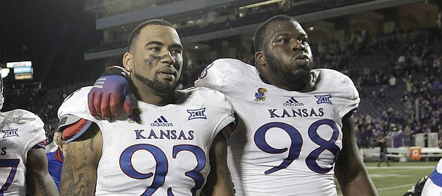 Kansas defensive lineman Ben Goodman (93) and Keon Stowers (98) walk off the field at the end of the Jayhawks 51-13 loss to the Kansas State Wildcats Saturday in Manhattan. .