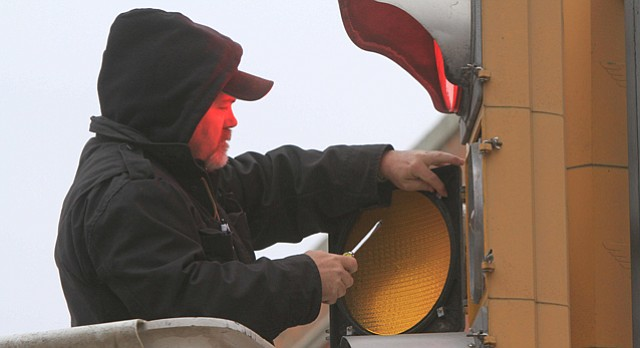 City employee Tommy Sutton installs a new LED traffic light at 9th and Massachusetts streets, Thursday, Feb. 9, 2012.