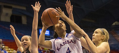 Kansas sophomore forward Jada Brown (4) looks for her shot after splitting Incarnate Word defenders Aelina Merritt (12) and Quincy Baker (24) during the first half of their game Thursday evening at Allen Fieldhouse.