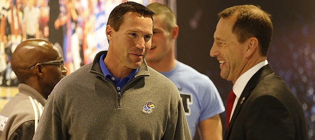 Defensive coordinator Clint Bowen, left, laughs with newly-hired Kansas head football coach David Beaty before Beaty is introduced to the Allen Fieldhouse crowd during halftime of the JayhawksÕ game against Floriday on Friday, Dec. 5, 2014. Beaty is the 38th head coach in the programÕs history.