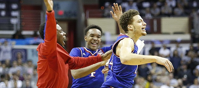 Kansas guard Brannen Greene, right, celebrates with teammates Devonte Graham, center, and Jamari Traylor during a timeout after a three by Greene in the second half on Wednesday, Dec. 10, 2014 at Verizon Center in Washington D.C.