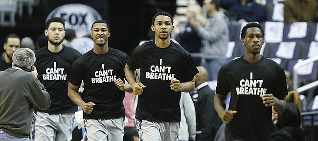 """Georgetown players take the court wearing """"I Can't Breathe"""" shirts in support of the family of Eric Garner before tipoff against Kansas on Wednesday, Dec. 10, 2014 at Verizon Center in Washington D.C. Garner, an unarmed black man died after being choked by a New York city police officer who was not indicted in a recent grand jury decision."""