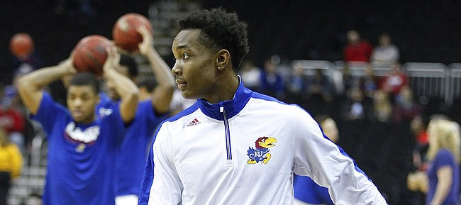 Kansas guard Devonte Graham watches warmups with a  boot on his right foot on Saturday, Dec. 13, 2014 at Sprint Center. It has been reported that Graham will be out four weeks with a toe injury.