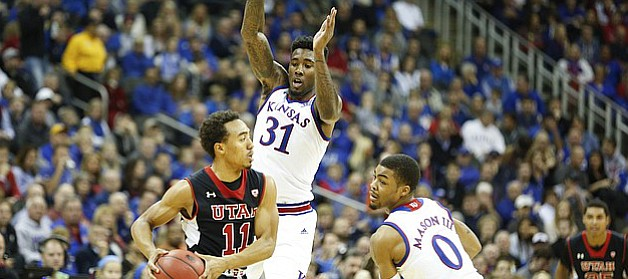 Kansas forward Jamari Traylor (31) and guard Frank Mason III defend against a pass from Utah guard Brandon Taylor (11) during the first half on Saturday, Dec. 13, 2014 at Sprint Center