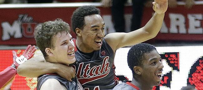 Utah Brandon Taylor, center, celebrates with Jakob Poeltl (42) and Delon Wright following an NCAA college basketball game against Wichita State, Wednesday, Dec. 3, 2014, in Salt Lake City. Utah won 69-68. (AP Photo/Rick Bowmer)