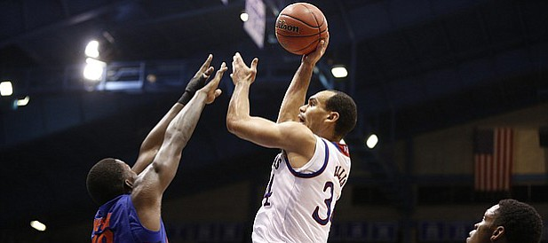 Kansas forward Perry Ellis (34) turns for a shot over Florida forward Dorian Finney-Smith (10) during the second half on Friday, Dec. 5, 2014 at Allen Fieldhouse.