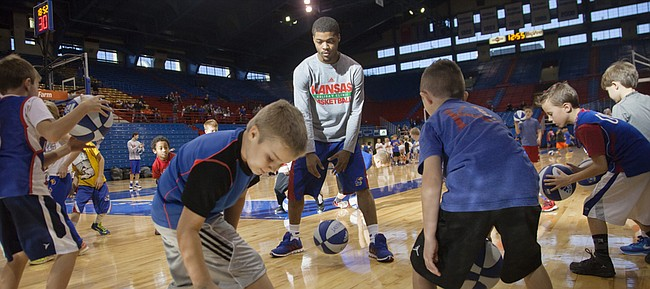 Young basketball players work on dribbling drills with Frank Mason III during the KU men's basketball Holiday Clinic Sunday, Dec. 28, 2014 at Allen Fieldhouse.
