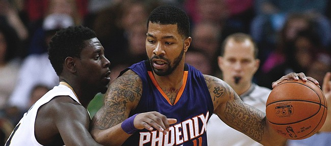Phoenix Suns forward Markieff Morris (11) drives against New Orleans Pelicans guard Jrue Holiday, left, during the second half of an NBA basketball game, Tuesday, Dec. 30, 2014, in New Orleans. The Pelicans won 110-106.