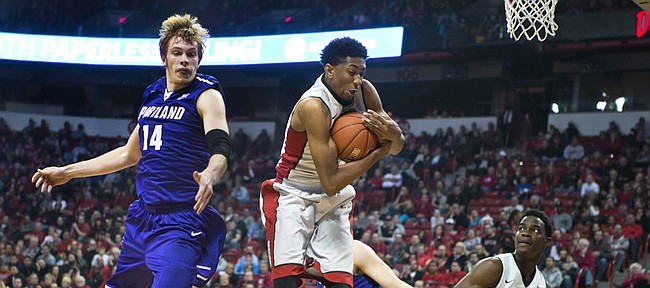 UNLV forward christian wood (5) secures the ball against Portland's Riley Barker on Dec. 17 in Las Vegas. Wood takes a 15.7-point scoring average and 9.8 rebound average into today's 3:30 p.m. game against Kansas in Allen Fieldhouse. Wood was named national player of the week last week.