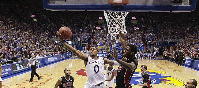 Kansas guard Frank Mason III (0) gets to the bucket past UNLV forward Goodluck Okonoboh (11) during the second half on Sunday, Jan. 4, 2015 at Allen Fieldhouse.