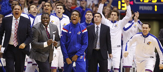 Injured Kansas guard Devonte Graham, center, and the rest of the bench react to a steal and a bucket by point guard Frank Mason during the first half against UNLV on Sunday, Jan. 4, 2015 at Allen Fieldhouse.