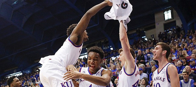 Kansas guard Devonte Graham (4) ducks under a leaping Kansas guard Wayne Selden Jr. after a bucket by reserve Christian Garrett during the second half on Saturday, Jan.10, 2015 at Allen Fieldhouse.