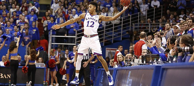 Kansas guard Kelly Oubre Jr. (12) looks to save a ball knocked out of bounds off the opening tip on Tuesday, Jan. 13, 2015 at Allen Fieldhouse.