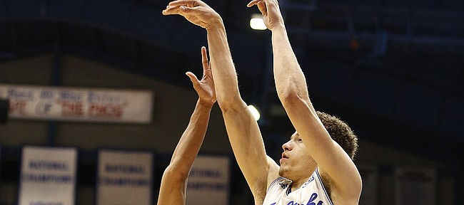 Kansas guard Brannen Greene (14) puts up a three from the corner as he is defended by Oklahoma guard Jordan Woodard (10) during the first half on Monday, Jan. 19, 2015 at Allen Fieldhouse.