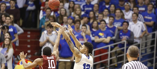 Kansas guard Kelly Oubre Jr. (12) puts up a three from the corner against Oklahoma guard Jordan Woodard (10) during the second half on Monday, Jan. 19, 2015 at Allen Fieldhouse.