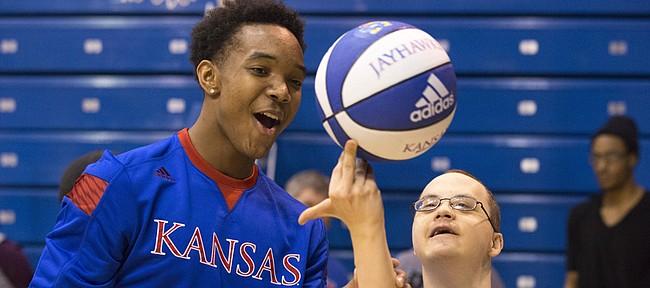 Kansas freshman Devonte' Graham teaches John Miller how to spin a basketball on his finger during the 31st annual Wilt Chamberlain Special Olympics clinic, Sunday at Allen Fieldhouse.