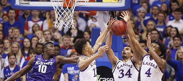 Kansas players Kansas guard Kelly Oubre Jr., left, forward Perry Ellis (34), and guard Devonte Graham (4) pull a rebound from Kansas State guard Malek Harris (10) during the first half on Saturday, Jan. 31, 2015 at Allen Fieldhouse.