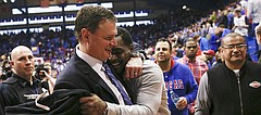 Kansas University head coach Bill Self gets a hug from former player Sherron Collins as the two head to the Jayhawks' locker room following the win against Kansas State on Saturday, Jan. 31, 2015 at Allen Fieldhouse.