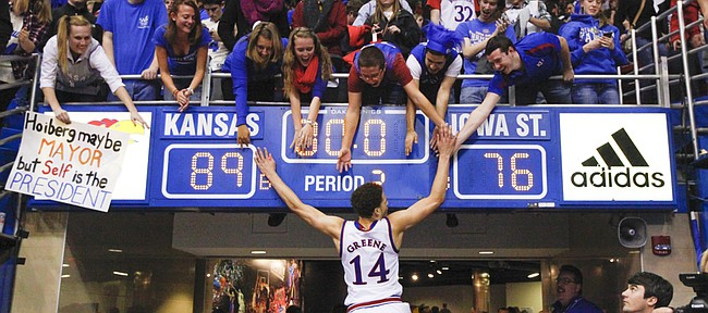 Kansas guard Brannen Greene slaps hands with the students seated above the scoreboard showing the Jayhawks' 89-76 victory over Iowa State on Monday, Feb. 2, 2015 at Allen Fieldhouse.