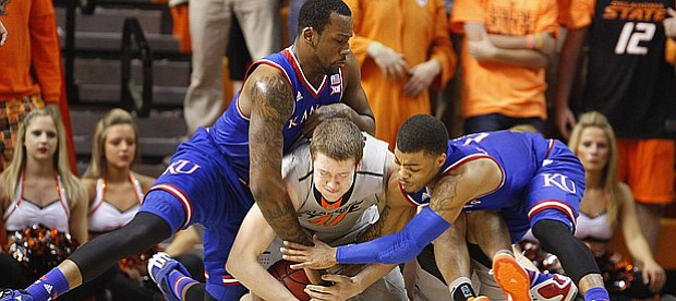 Kansas forward Cliff Alexander, left, and guard Frank Mason III collapse on top of Oklahoma State forward Mitchell Solomon (41) as they compete for control of a loose ball during the first half on Saturday, Feb. 7, 2015 at Gallagher-Iba Arena.