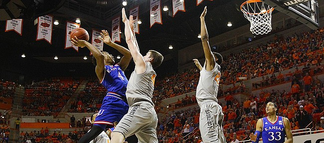 Kansas guard Devonte Graham (4) is defended by Oklahoma State forward Mitchell Solomon, left, and forward Leyton Hammonds during the second half on Saturday, Feb. 7, 2015 at Gallagher-Iba Arena.