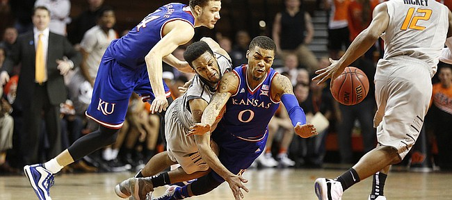 Oklahoma State forward Leyton Hammonds (23) knocks the ball away from Kansas guard Frank Mason III (0) to Oklahoma State guard Anthony Hickey Jr. (12) late in the second half on Saturday, Feb. 7, 2015 at Gallagher-Iba Arena. At right is Kansas guard Brannen Greene.