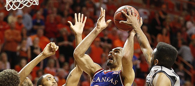 Kansas forward Perry Ellis (34) has his shot blocked by Oklahoma State forward Leyton Hammonds late in the second half on Saturday, Feb. 7, 2015 at Gallagher-Iba Arena. Also pictured are Oklahoma State center Michael Cobbins (20) and Kansas guard Brannen Greene.