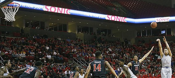 Kansas guard Brannen Greene (14) shoots a three-point basket against Texas Tech during the first half Tuesday, Feb. 10, 2015 at United Supermarkets Arena.