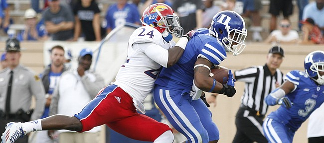 Kansas cornerback JaCorey Shepherd jumps on the back of Duke running back Josh Snead after a catch during second quarter on Saturday, Sept. 13, 2013 at Wallace Wade Stadium in Durham, North Carolina.
